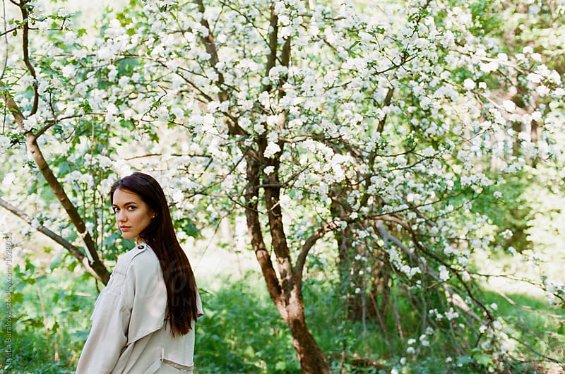 Young woman t cherry blossom tree by Lyuba Burakova for Stocksy United
