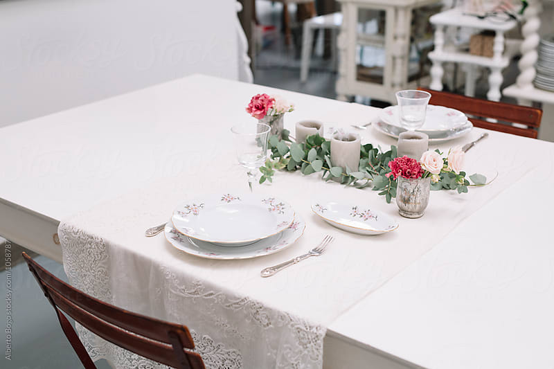 Table setup with flower and candle by Alberto Bogo for Stocksy United