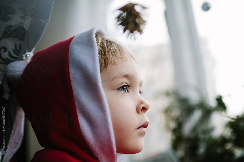 Little girl in a red and white hood look out of the window. by Julia Forsman for Stocksy United