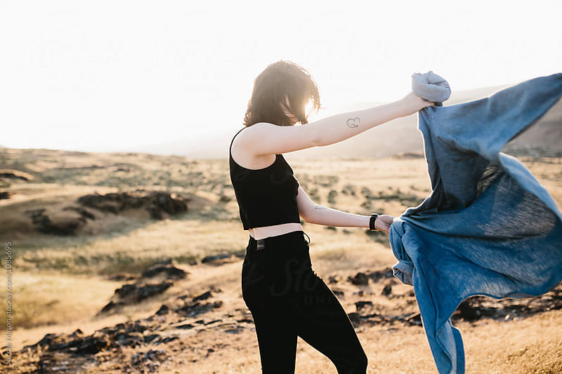 woman putting on denim shirt on windy day at sunset by Nicole Mason for Stocksy United