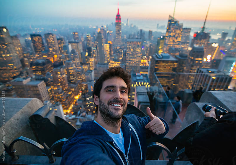 Smiling man taking selfie against of New York cityscape by Alejandro Moreno de Carlos for Stocksy United