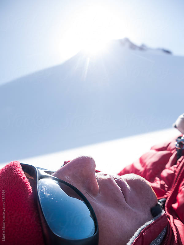 Headshot of exhausted alpinist lying under the snowy mountain by Martin Matej for Stocksy United