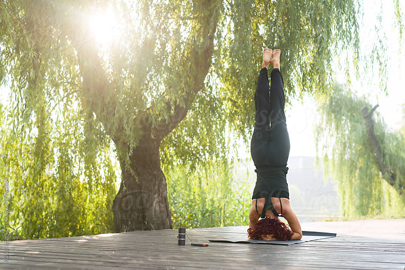 Woman doing a headstand outdoor in a park by RG&B Images for Stocksy United