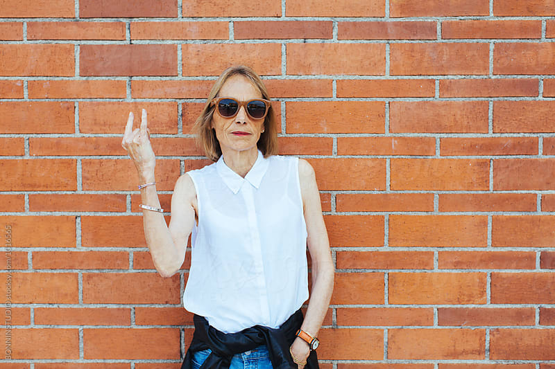 Serious senior woman doing the rock 'n' roll sign in front of a brick wall. by BONNINSTUDIO for Stocksy United