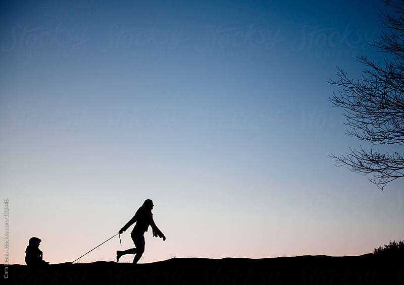Silhouette of a mother pulling her child in a sled across a field in winter by Cara Dolan for Stocksy United