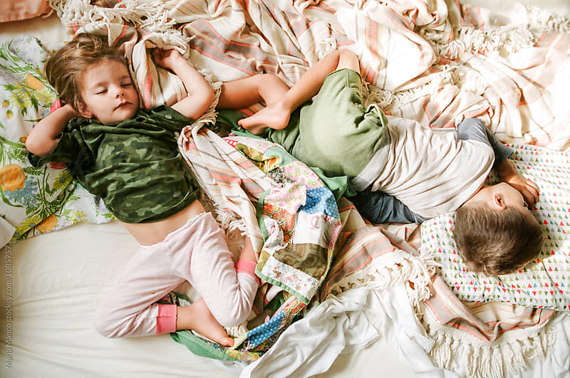 overhead shot of kids sleeping on bed by Maria Manco for Stocksy United