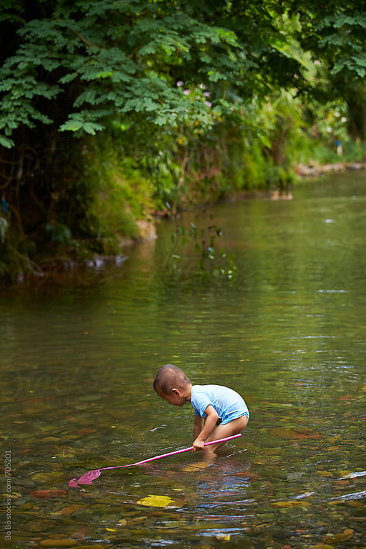 little asian boy capture fish in the stream by Bo Bo for Stocksy United