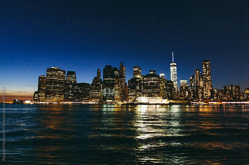 View of New York city at night from Brooklyn over Hudson river by Alejandro Moreno de Carlos for Stocksy United