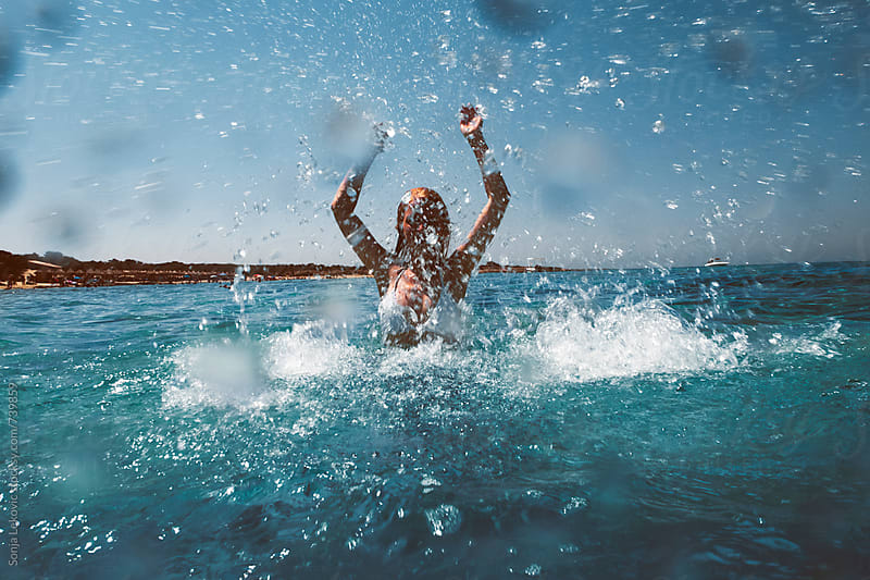 woman in white bikini in sea water splash by Sonja Lekovic for Stocksy United