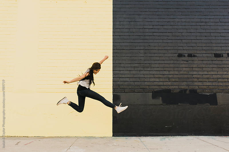 Young woman jumping in air by Isaiah & Taylor Photography for Stocksy United