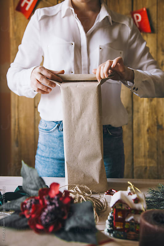 Woman wrapping Christmas gift by Danil Nevsky for Stocksy United
