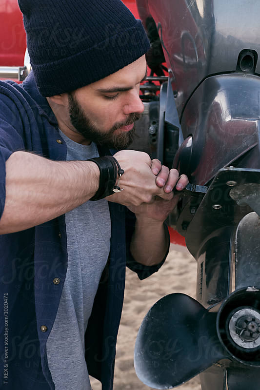 Close-up of bearded man in hat repairing motor of boat by T-REX & Flower for Stocksy United