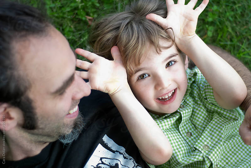 Little boy and his dad play together in the grass by Cara Dolan for Stocksy United