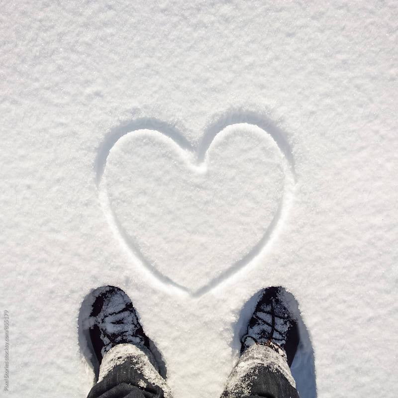 Person standing in front of snow heart by Pixel Stories for Stocksy United