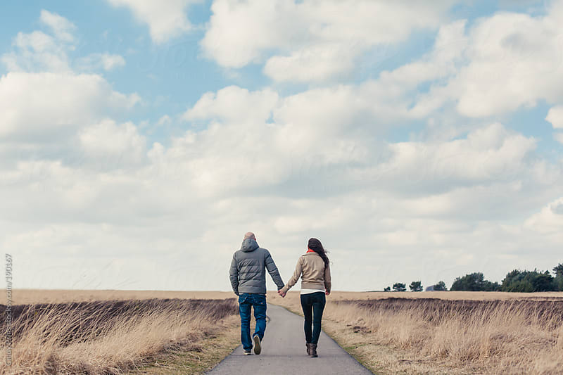 Couple holding hands and walking away on a path in a field ...