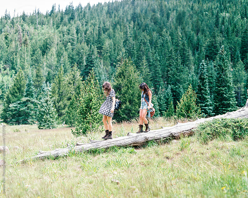 Two friends walking on log by Daniel Kim Photography for Stocksy United