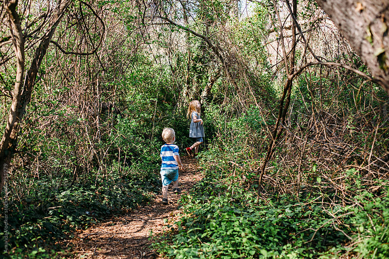 Two Young Children Exploring in the Woods by Amanda Voelker for Stocksy United