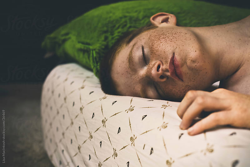 red haired boy with freckles and cleft chin, sleeping on bed with pirate sheets by Lisa MacIntosh for Stocksy United