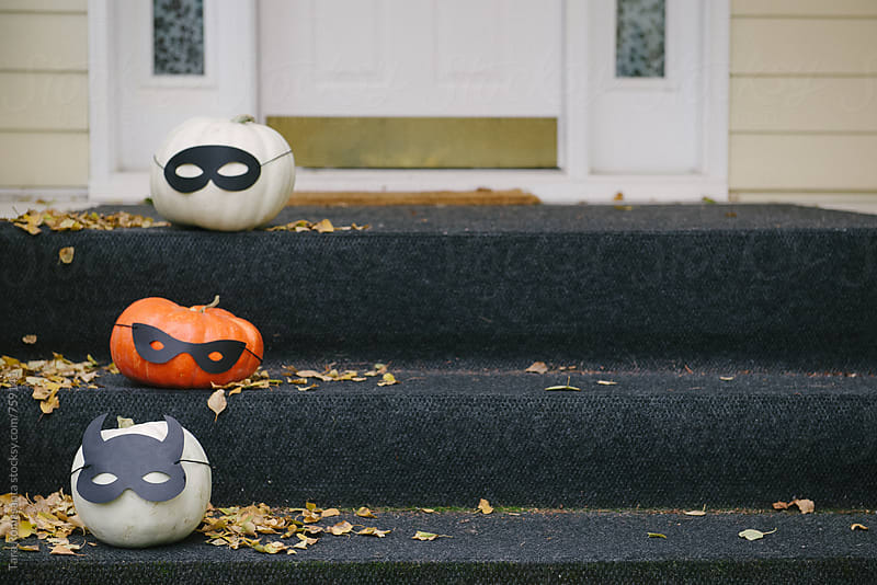 three decorated pumpkins on steps by Tara Romasanta for Stocksy United