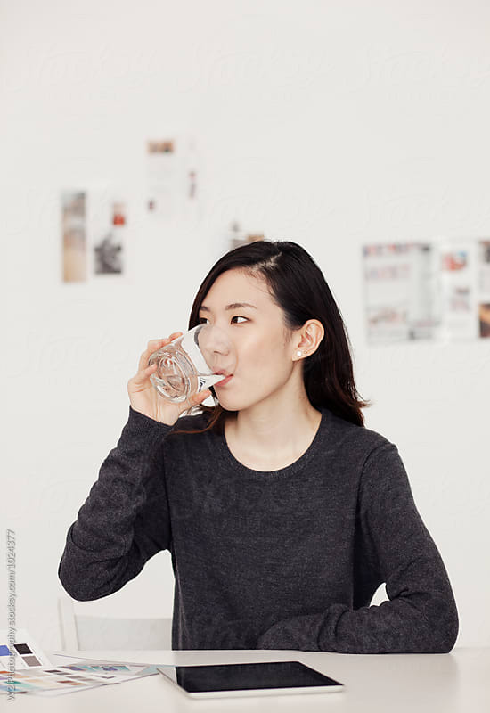 Young woman drinking water at her desk. by W2 Photography for Stocksy United