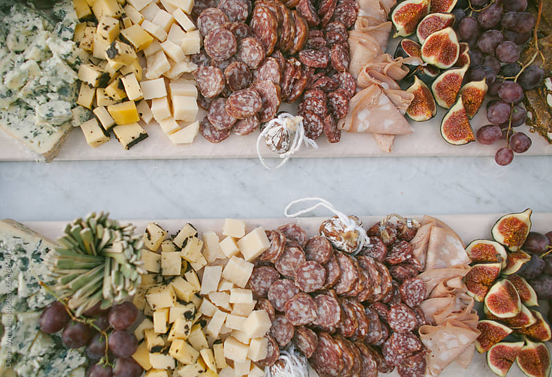 A platter with cheese, meat and figs cut up  by Denni Van Huis for Stocksy United