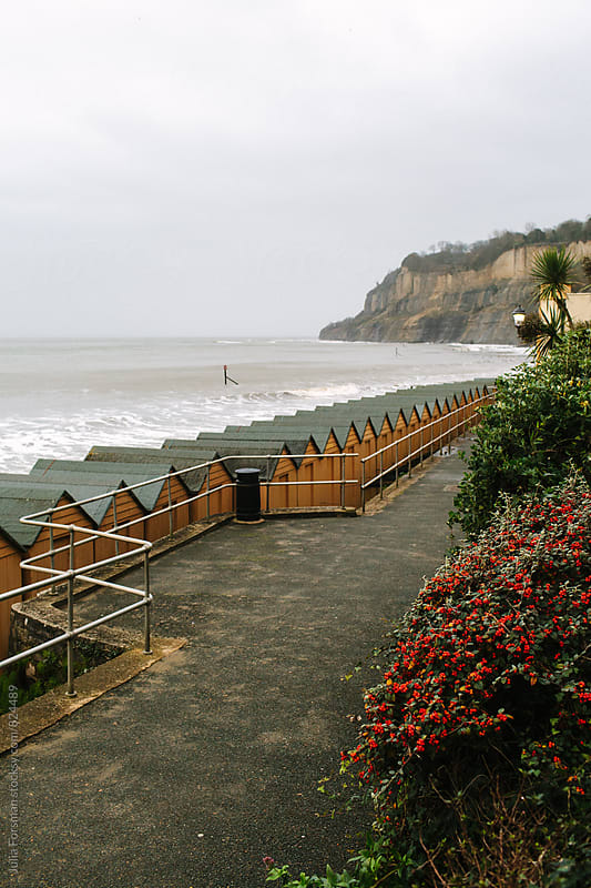 A path, beach huts and distant cliffs in an English seaside town. by Julia Forsman for Stocksy United