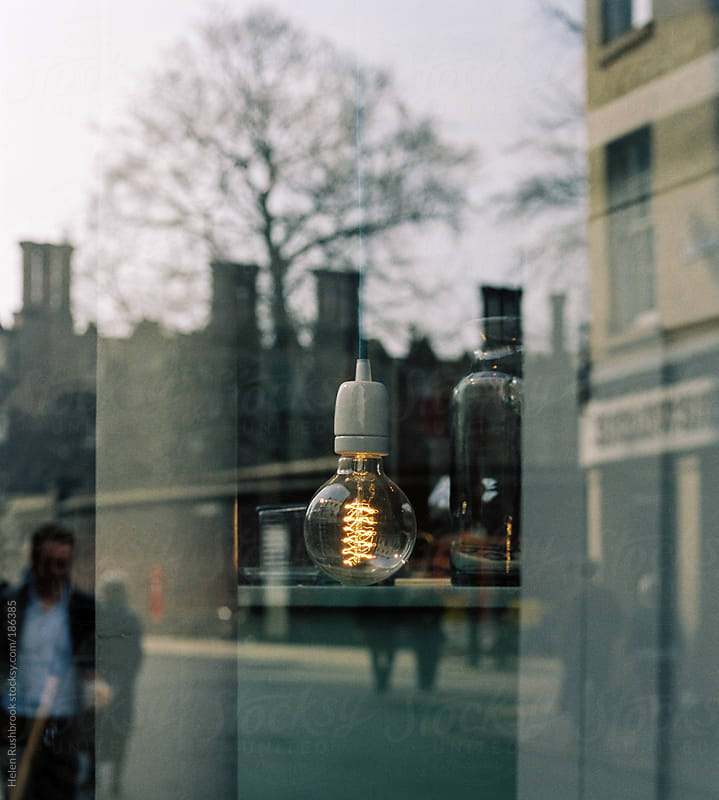 A lightbulb seen through a shop window by Helen Rushbrook for Stocksy United