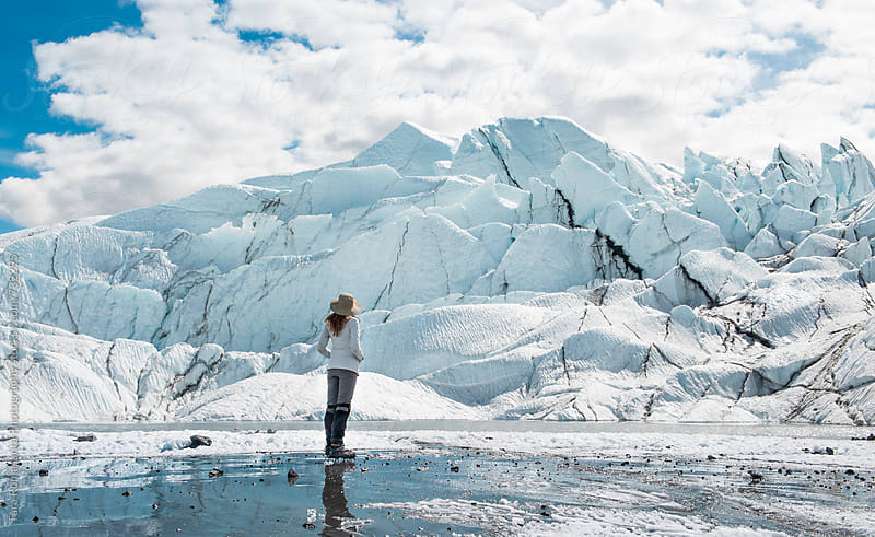 woman stands looking at the face of Matanuska Glacier in Alaska by Tara Romasanta for Stocksy United