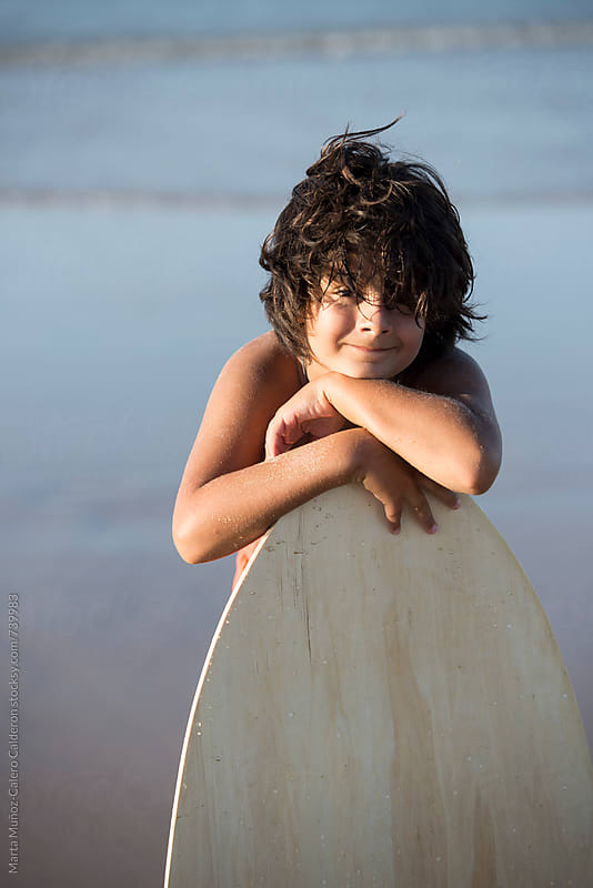 Boy holding a Surf slide board by Marta Muñoz-Calero Calderon for Stocksy United