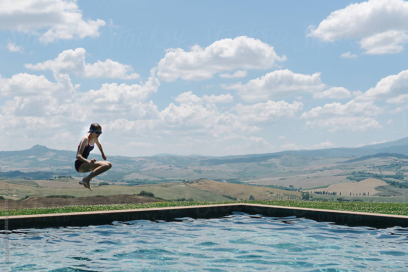 Girl jumping into pool in Tuscany by Kirstin Mckee for Stocksy United