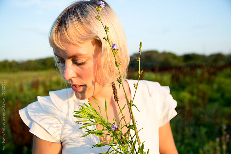 Woman picking flowers by Ann-Sophie Fjelloe-Jensen for Stocksy United