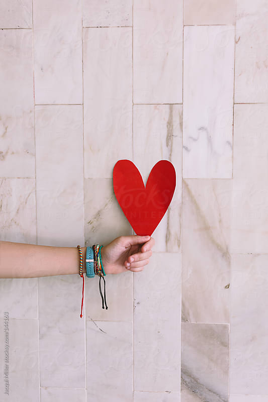 Young teen girl holding a red paper heart in front of a tiled wall.  by Jacqui Miller for Stocksy United