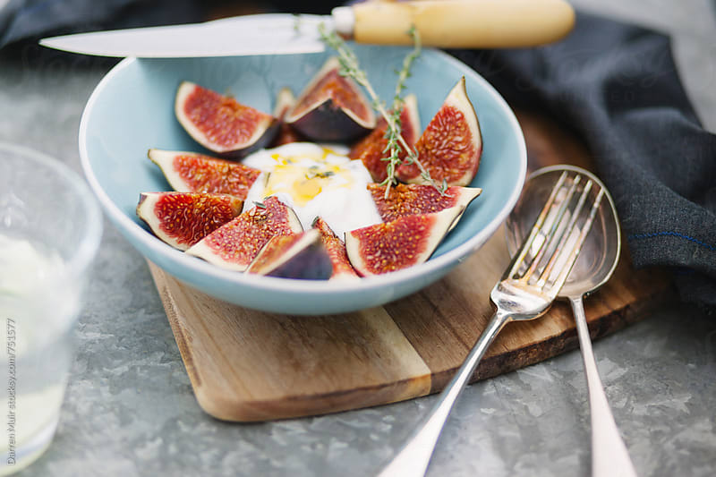 A bowl of figs with yogurt and honey and thyme. by Darren Muir for Stocksy United