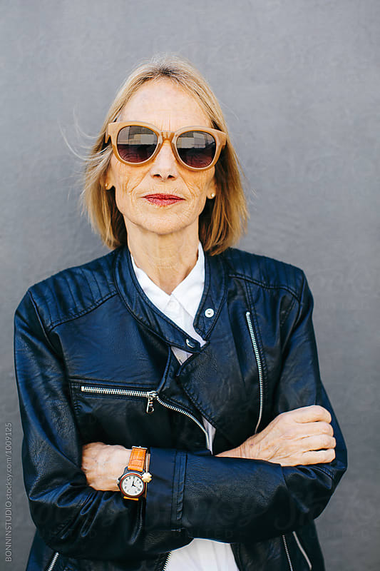 Portrait of a senior woman wearing a leather jacket and sunglasses.  by BONNINSTUDIO for Stocksy United