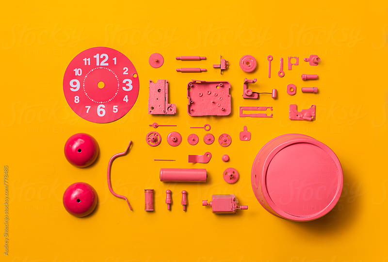 Organised Disassembled Clock/pink parts on orange background by Audrey Shtecinjo for Stocksy United