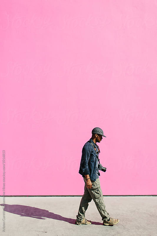 A young man with a camera walking by a hot pink wall.  by Kristen Curette Hines for Stocksy United