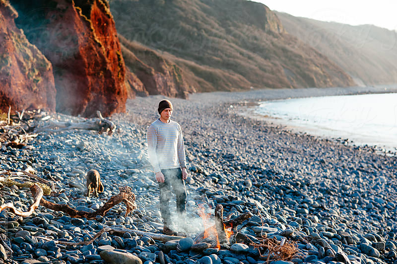 Man standing next to a fire on a beach by Suzi Marshall for Stocksy United