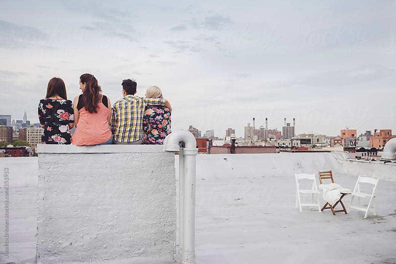 Friends Hanging Out Watching the World From a New York Rooftop by Joselito Briones for Stocksy United