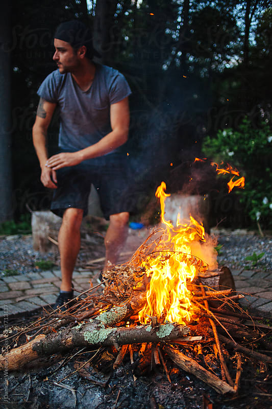 A caucasian man tending to a campfire outdoors in the evening. by J Danielle Wehunt for Stocksy United