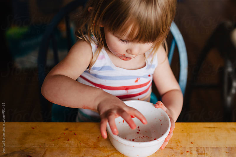 Toddler girl eating red jello by Jessica Byrum for Stocksy United