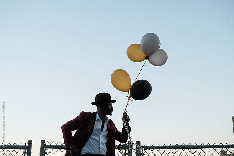 Young dapper male holding balloons by Eddie Pearson for Stocksy United