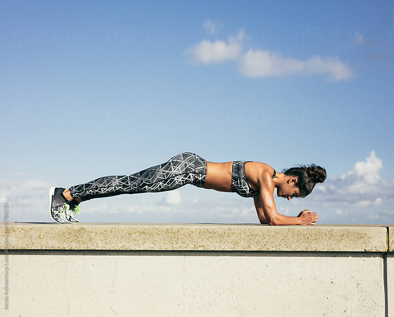 Woman doing plank exercise outdoors by Jacob Lund for Stocksy United