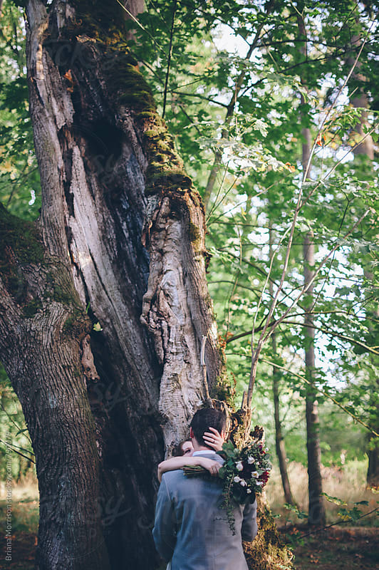 Anonymous Couple Embracing in front of a Tree by Briana Morrison for Stocksy United