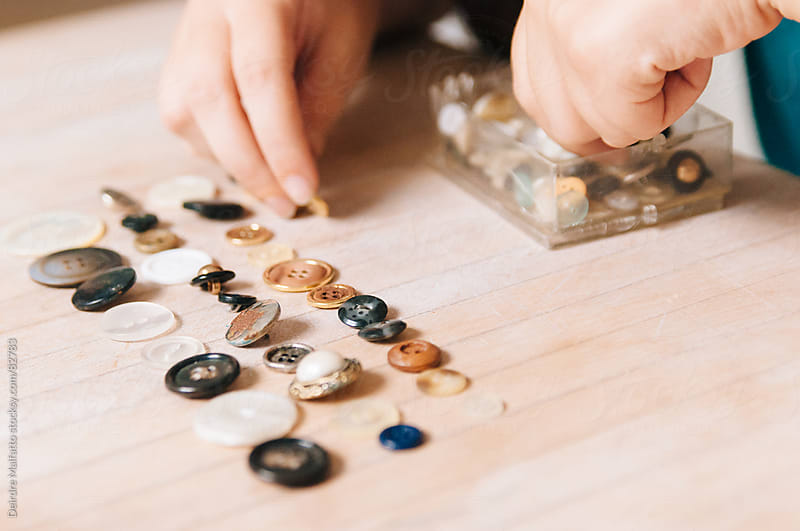 hands sorting vintage buttons by Deirdre Malfatto for Stocksy United