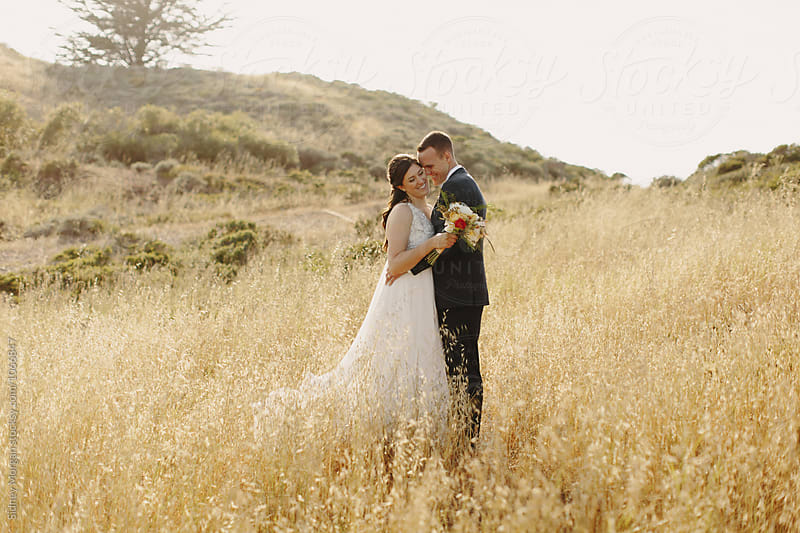 Groom Kissing Bride in Field by Sidney Morgan for Stocksy United