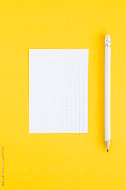 White pencil and note card on yellow background by Melanie Kintz for Stocksy United