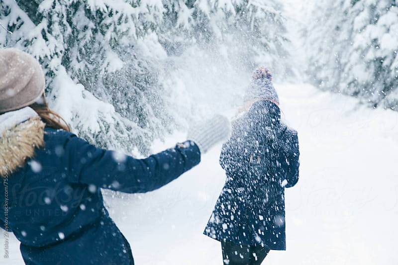 Female couple enjoying snowball fight by Borislav Zhuykov for Stocksy United