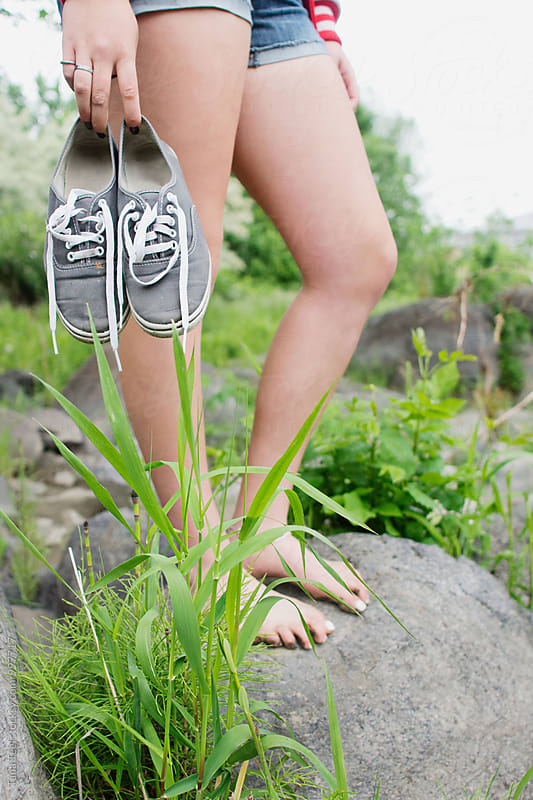 barefoot teenager standing on rock holding tennis shoes by Tana Teel for Stocksy United