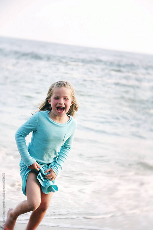 Girl at beach wearing blue dress in motion and laughing by Dina Giangregorio for Stocksy United