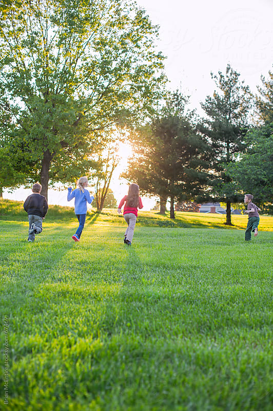 Children Playing in Backyward at Sunset by Brian McEntire for Stocksy United